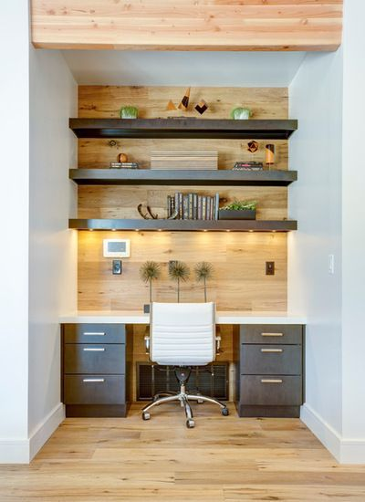 This handsome home office has engineered wood flooring that extends right up the wall to the ceiling, creating a warm textured accent. Charcoal floating shelves and cabinets provide contrast while a classic Eames task chair offers ergonomic modern style.
