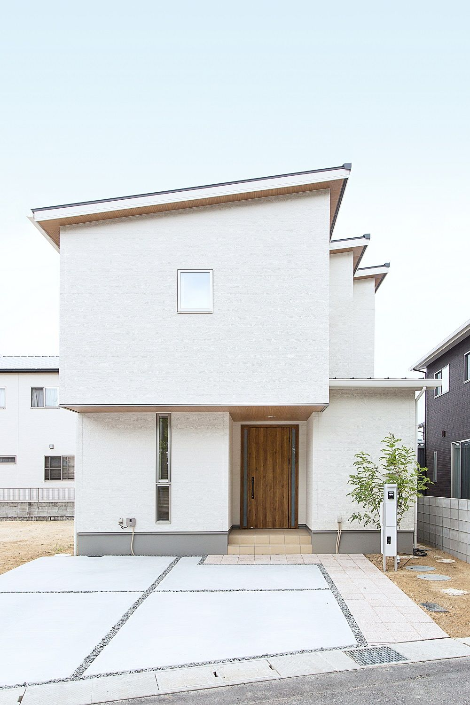 ヘルシーホーム 設計士とつくる家 白色の外壁に木目の軒天と玄関ドアで