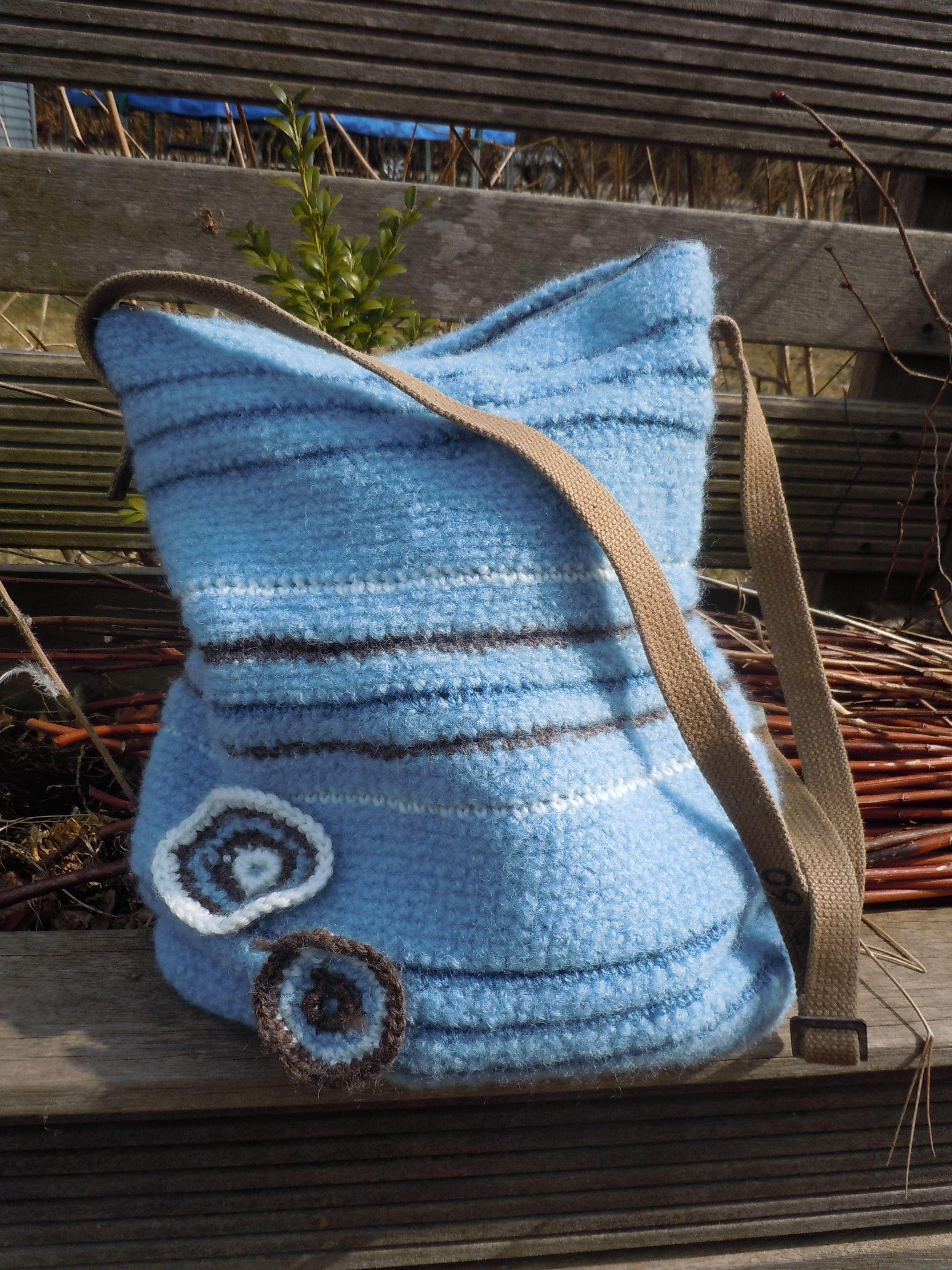 Hæklet og filtet taske med foer. 26 cm bred for oven, 31 cm bred for neden. 37 cm høj. Lukkes med lynlås. Regulerbar strop af gammel militærstrop. Strikket af garnet fra et par ærmer på en genbrugt sweater. Kr 200