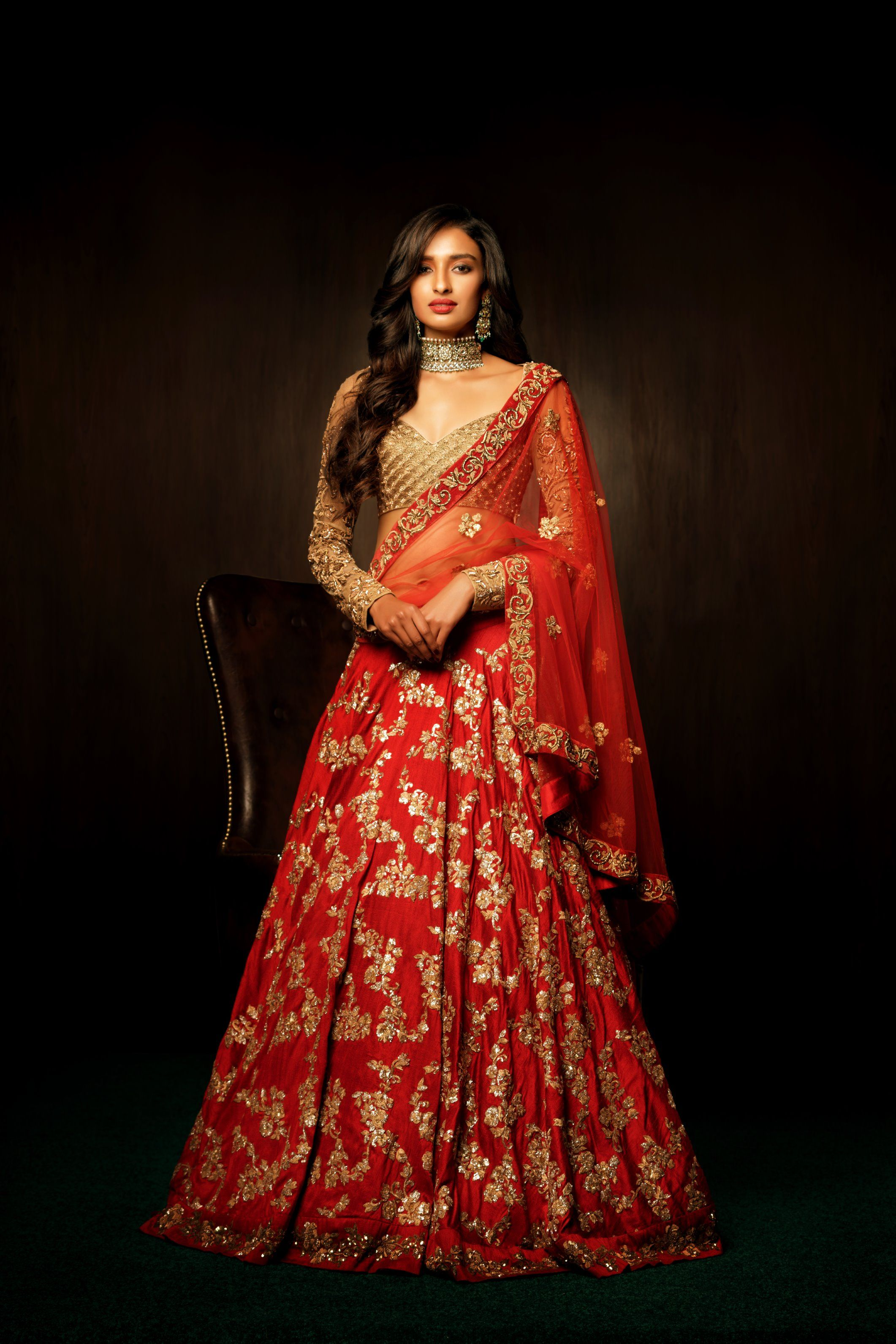 A sophisticated bias cut tango red lehenga with a spray of floral