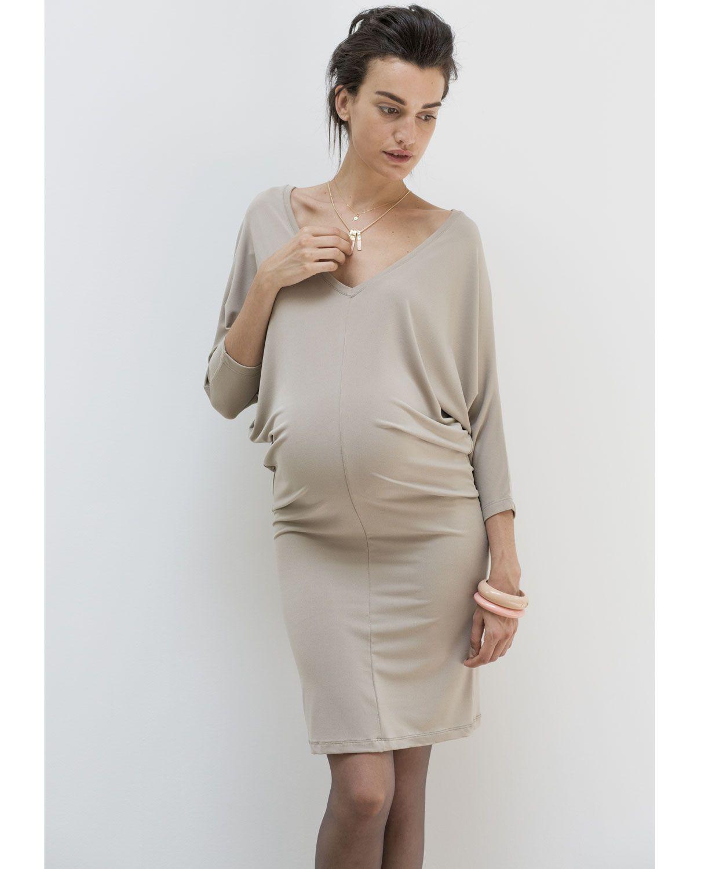 Vestido corto de #embarazada en punto crep elástico de color arena con manga murciélago, cuello de pico y lazada trasera. El corte de este vestidoestiliza la figura gracias a su forma triangular.