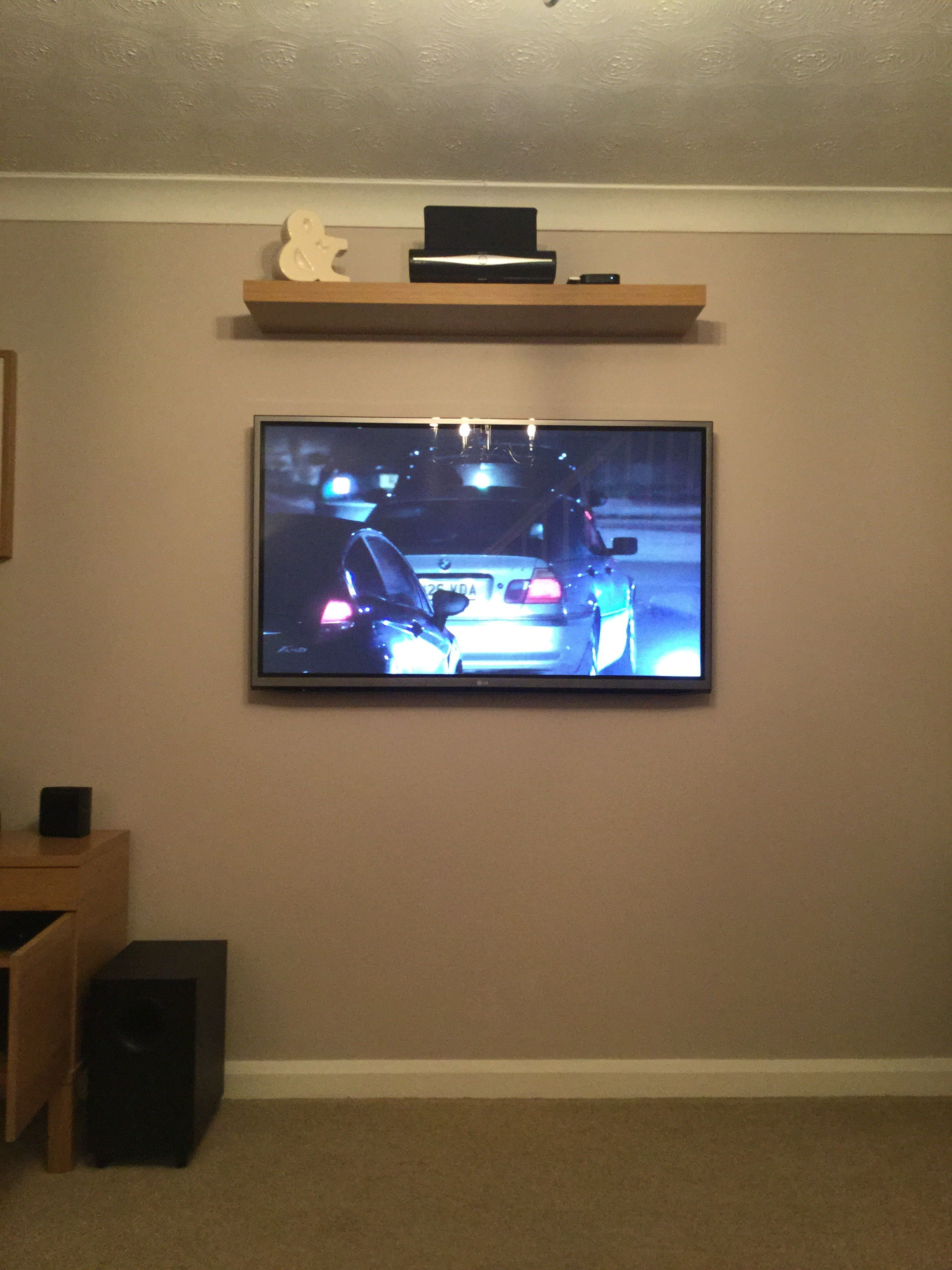 Tv on the wall with cable/satellite receiver on the shelf