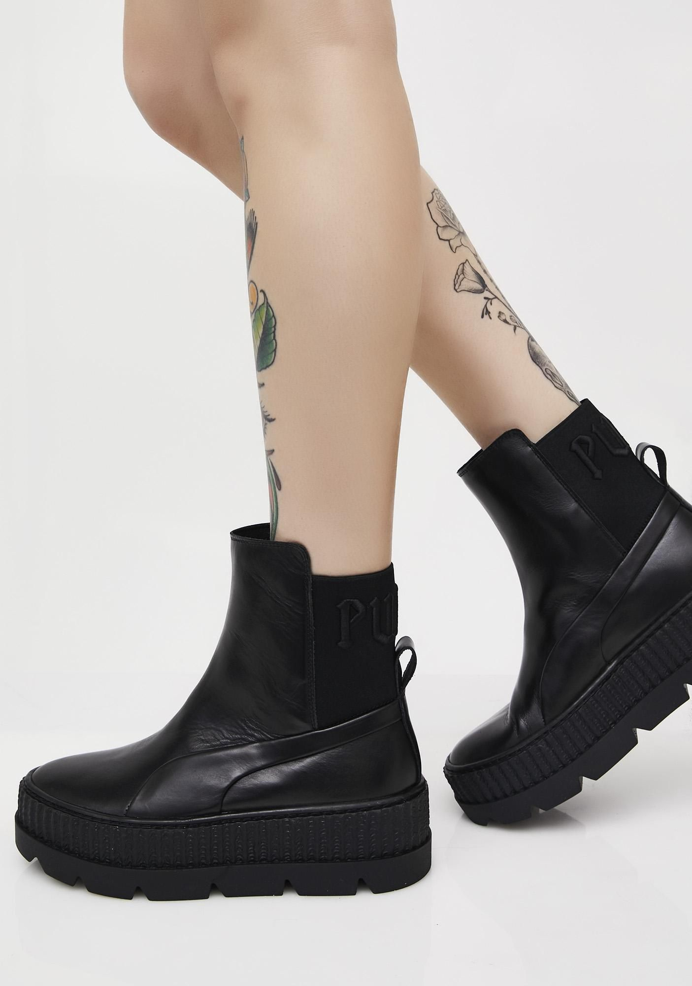 "18cfd708399c17 PUMA FENTY PUMA By Rihanna Chelsea Sneaker Boots got ya on another level.  These black sneaker boots have thikk soles and ""PUMA"" text on the back."