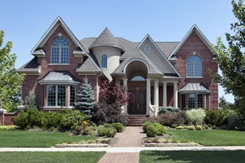 front yard landscaping of a brick home with turret and