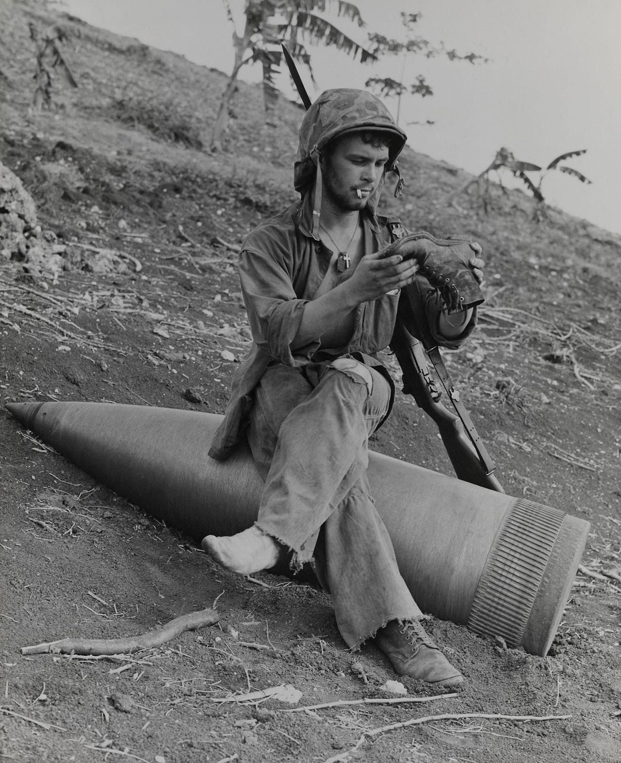"""error888:  """"""""Sittin' On Top of the World."""" Of all things, Marine Private First Class Raymond L. Hubert, of Detroit, Michigan, chooses a huge unexploded naval shell for a sofa as he removes a three day accumulation of Saipan sand from his field shoes...."""