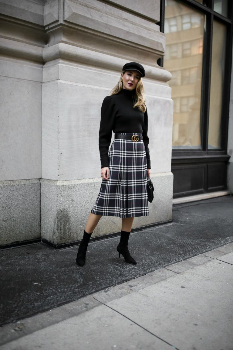 fdf4d2ca3b2d Mary Orton of Memorandum wears a Burberry plaid checked midi skirt, a black  puffed-shoulder turtleneck, black Stuart Weitzman sock boots and a black  baker ...