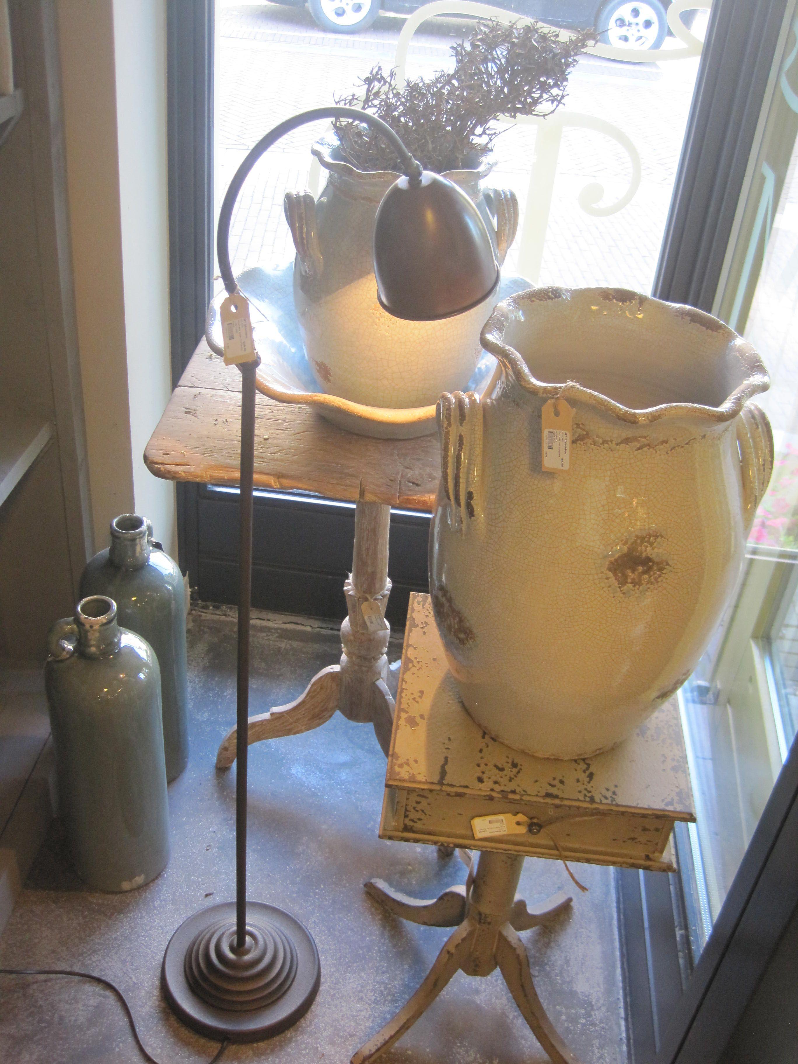 Kruiken op bijzettafeltjes met brocante lamp en siertak.