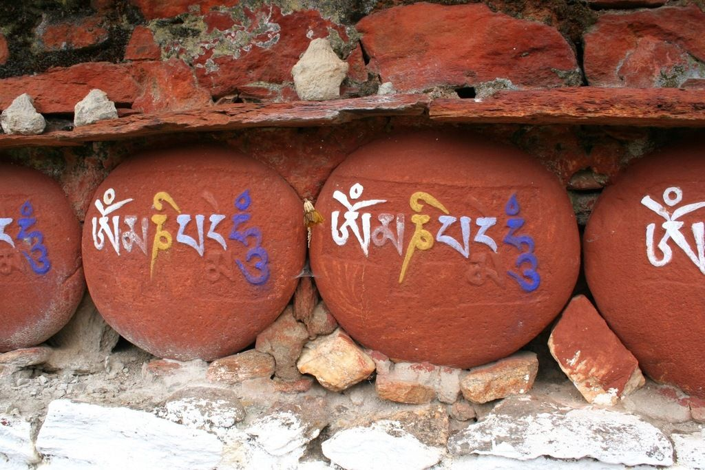 """Mani stones are inscribed with the six syllabled mantra of Avalokiteshvara (Om mani padme hum, hence the name """"Mani stone""""), as a form of prayer in Tibetan Buddhism."""