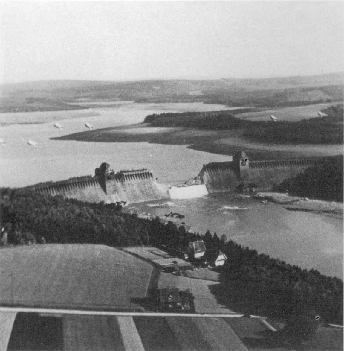 """Water continues to pour through the Möhne Dam (seen from a low flying RAF photo reconnaissance Supermarine Spitfire) after it was struck the previous night by an """"Upkeep"""" bouncing bomb dropped from a British Avro Lancaster heavy bomber during the now famous """"Dambuster"""" raid. Ruhr, Germany. 18th of May 1943."""
