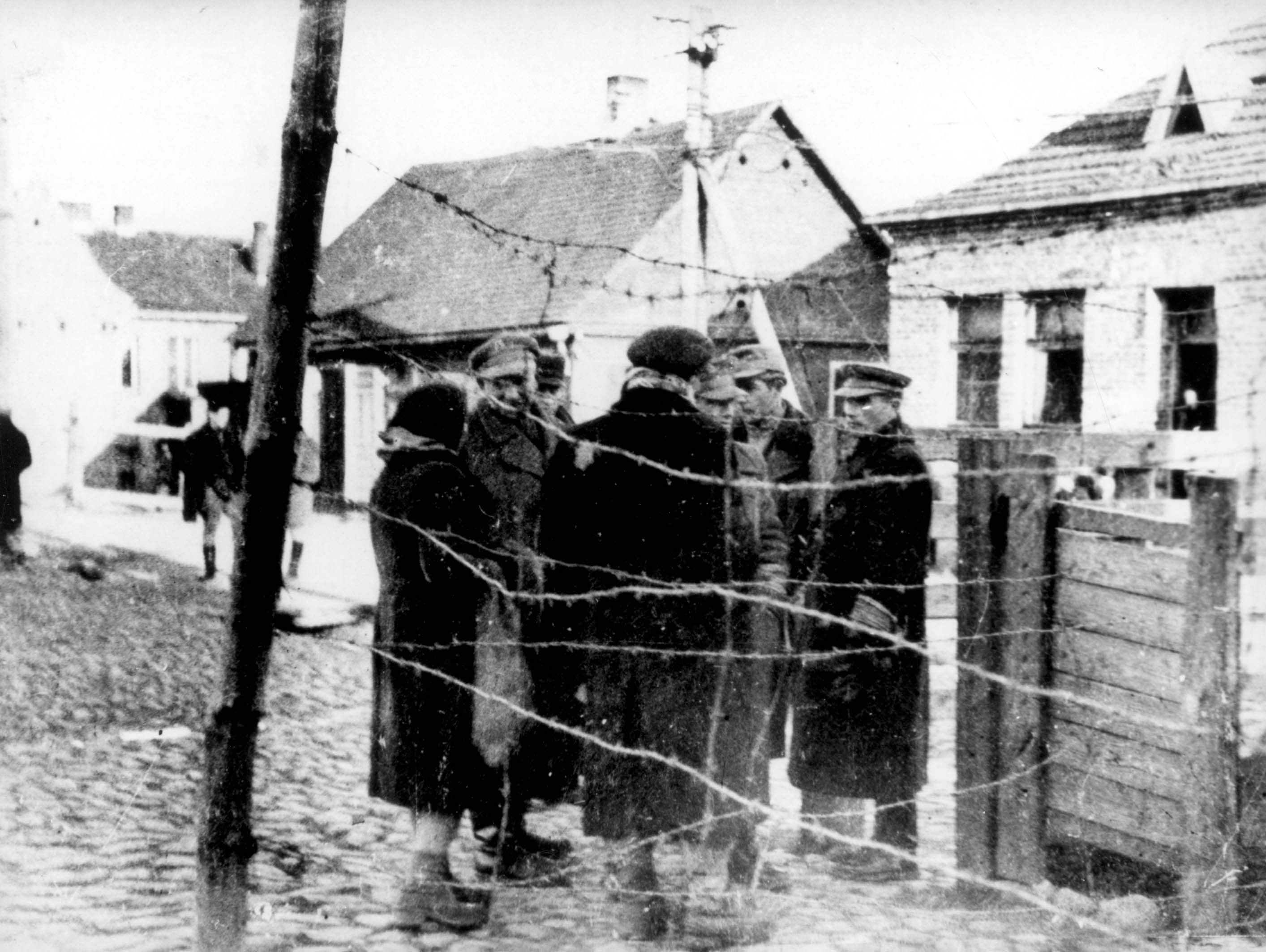 Kovno, Lithuania, A group of people standing beside a barbed wire fence.