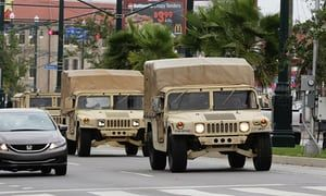 Louisiana national guard vehicles roll down a street in New Orleans.