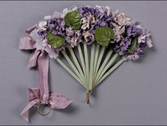 Bouquet fan. Purple and lavendar silk violets with glazed green leaves attached to green silk leaf with lavendar pinked silk edging. Pale green wood sticks. Decorative brass ring. Lilac silk ribbon to left ties in bows at top and at decorative brass ring which slides up to secure fan in bouquet form.  Souvenir of International Exposition, Paris, 1900