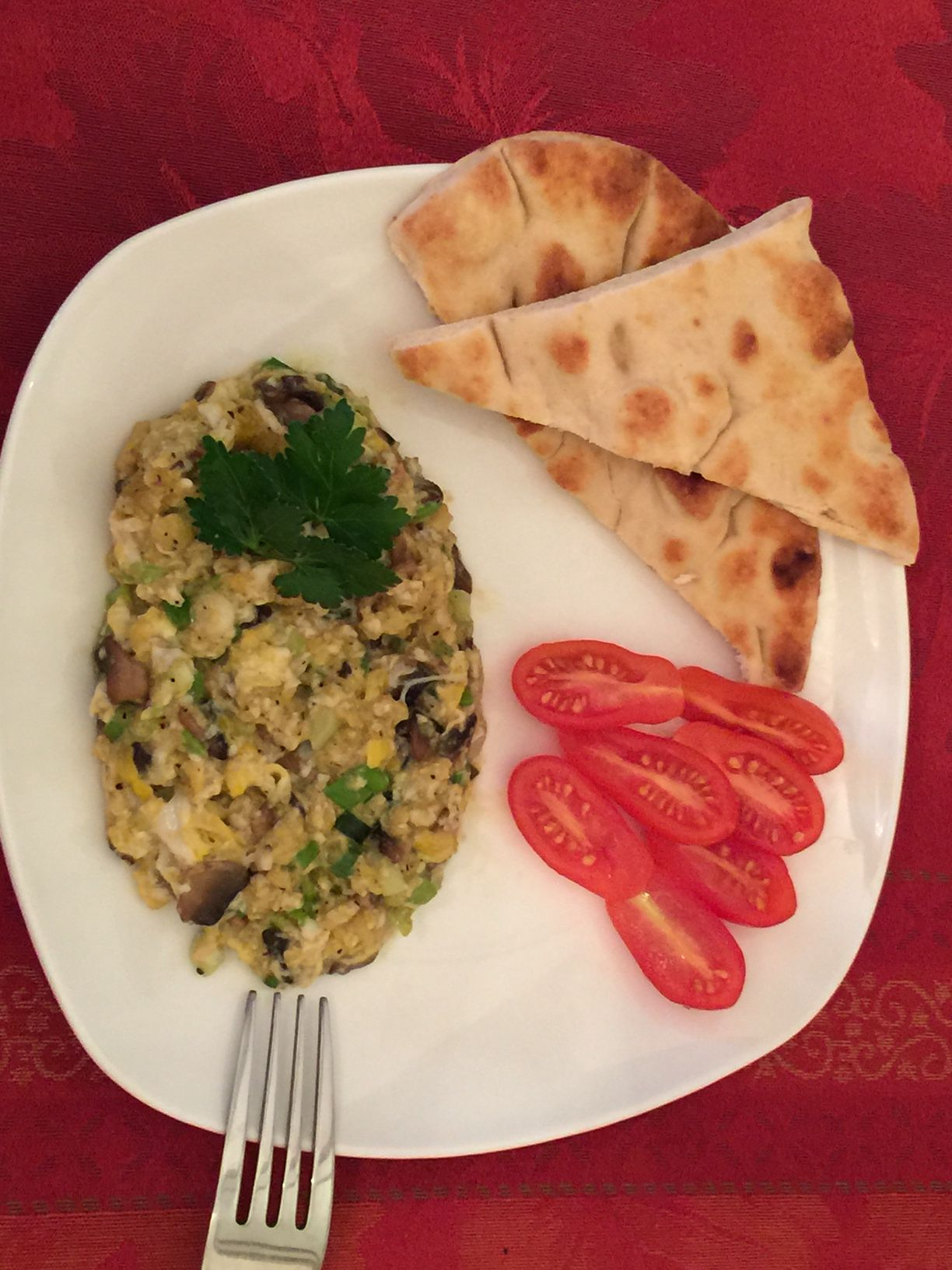 Creamy scrambled eggs with mushrooms and scallions served with toasted naan bread.