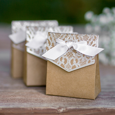 """Bring some old time allure to your wedding day with our Naturally Vintage Tent Favor Boxes. These DIY wedding favors are perfect for holding candy or small treats. The lace detail and darling ribbon really put the finishing touch these boxes!Kraft tent style favor box with silver foil lace design. Includes 5/8"""" and 12"""" long white satin ribbon. Package of 25. 3.75"""" x 3"""" x 1.375""""."""