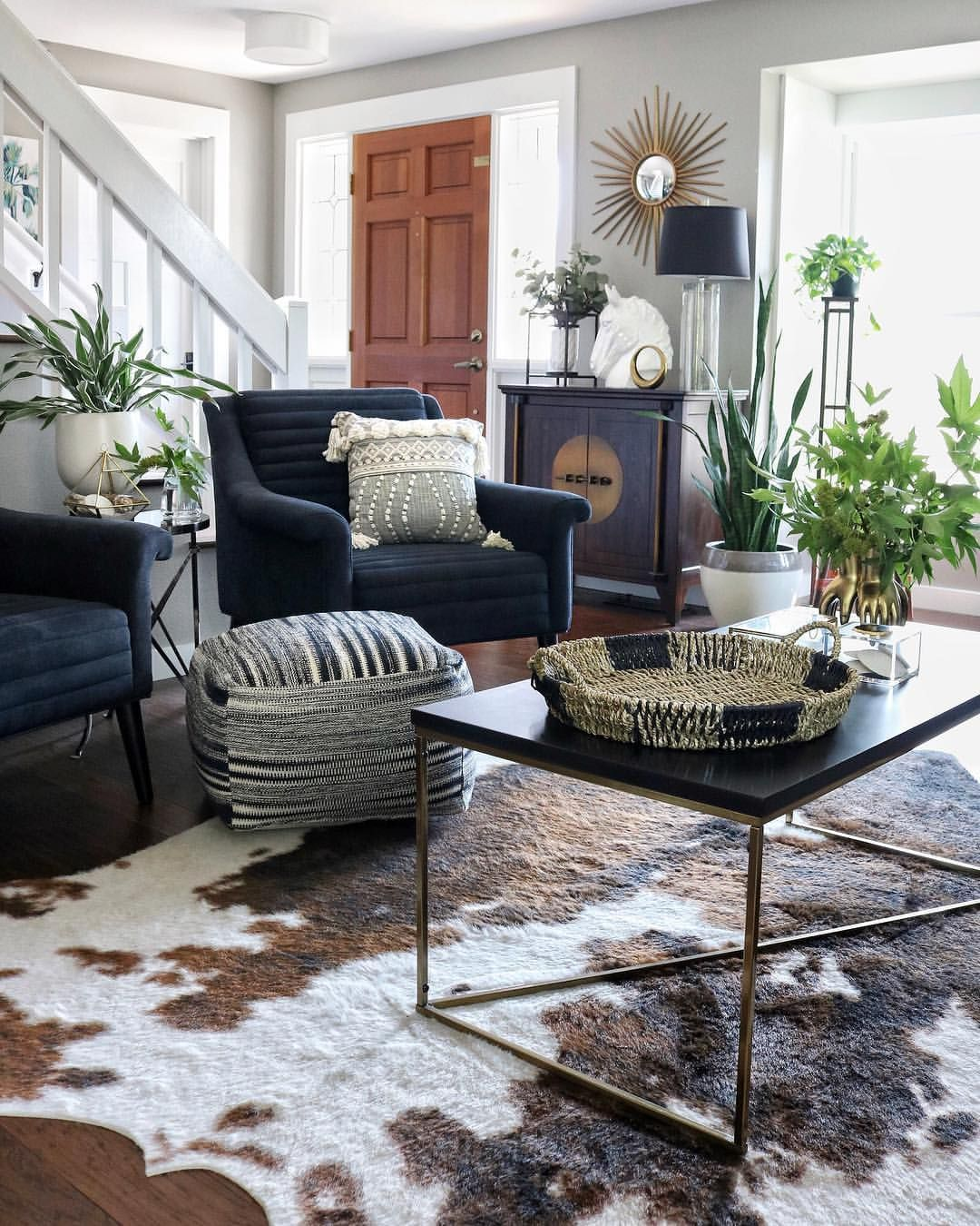 Living room with striped pouf, faux cow hide, & plants