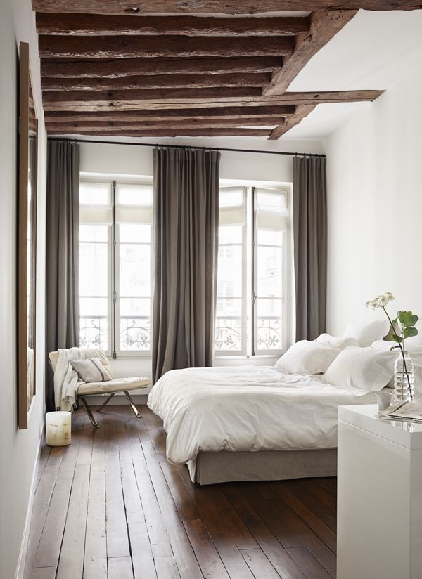 neutral bedroom with white walls rustic exposed wood beams and