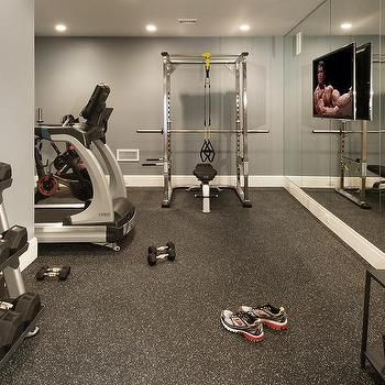 basement gym with flat panel tv on mirrored walls  home