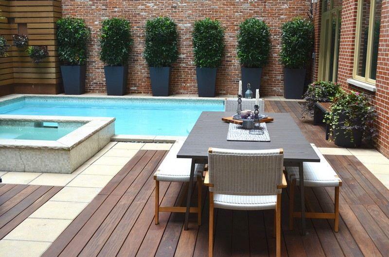 piscine avec plage en bois composite sur la terrasse avec coin repas mur de brique