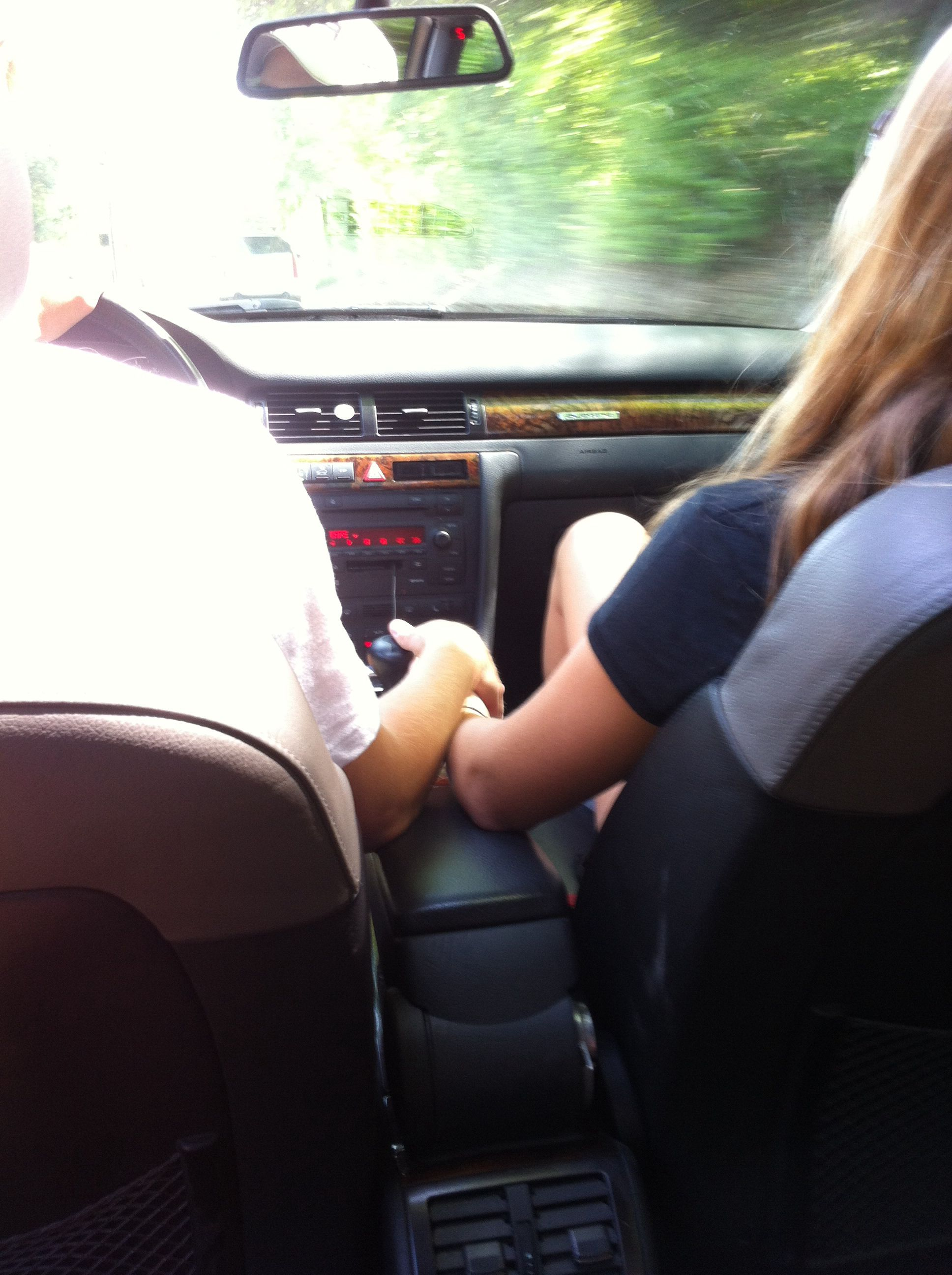 Boyfriend And Girlfriend Holding Hands While Driving In A