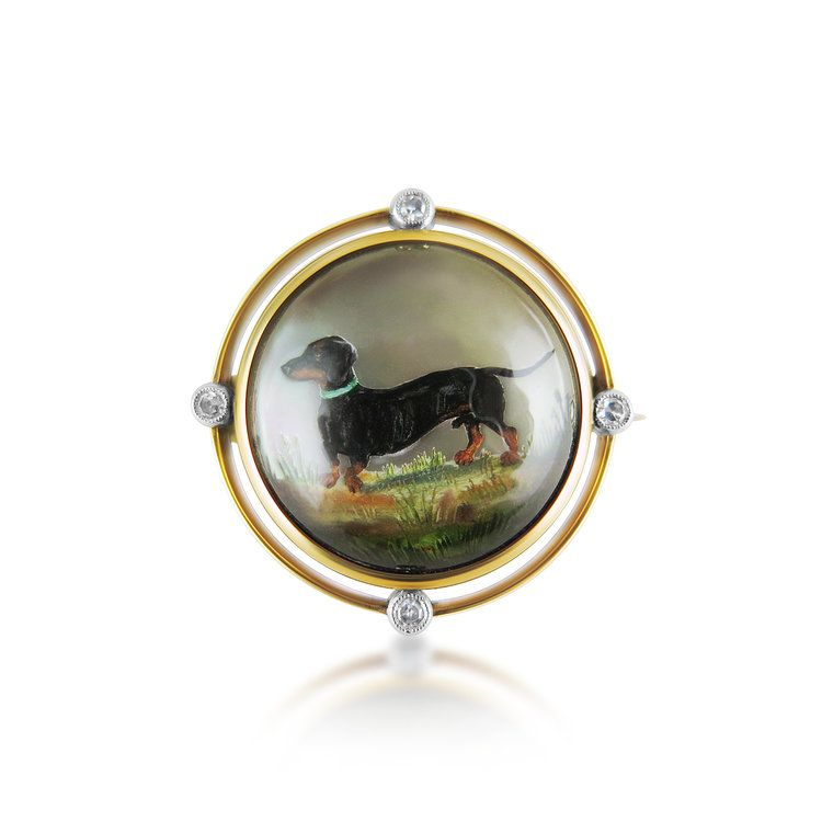 ANTIQUE GOLD, DIAMOND AND MOTHER-OF-PEARL REVERSE CRYSTAL INTAGLIO BROOCH  The circular crystal depicting a Dachshund, four diamond points to the outer frame.