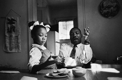 """King said in an interview that this photograph was taken as he tried to explain to his daughter Yolanda why she could not go to Funtown, a whites-only amusement park in Atlanta. King claims to have been tongue-tied when speaking to her. """"One of the most painful experiences I have ever faced was to see her tears when I told her Funtown was closed to colored children, for I realized the first dark cloud of inferiority had floated into her little mental sky."""" (TIME)"""