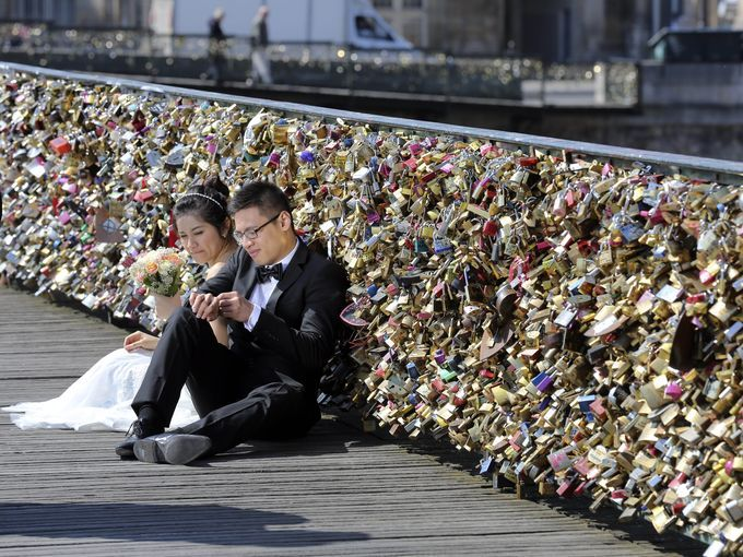 A newlywed couple sit on the Pont des Arts in Paris