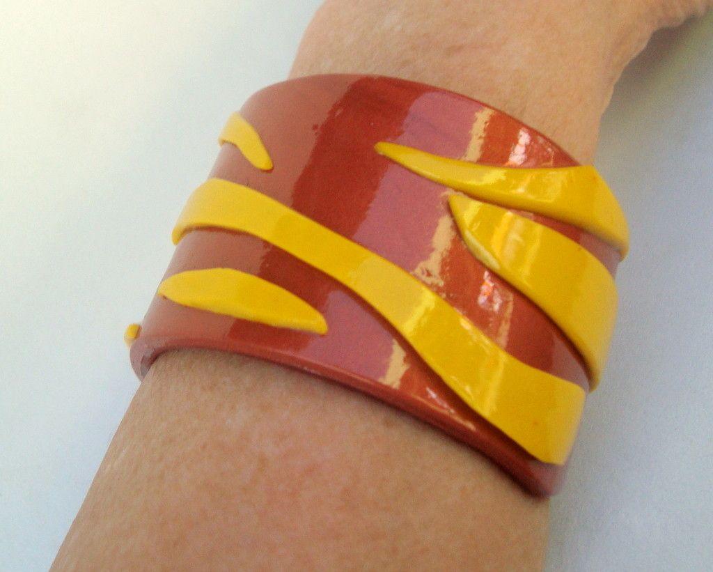 Bracelete totalmente feito a mão, em cerâmica plástica, na cor cobre com detalhes amarelos. Adapta-se ao braço, sem fecho (por pressão natural do produto), sendo muito´fácil de colocar e tirar. <br>Por ser artesanal, é uma peça exclusiva. <br>Ideal para braços com até 19 cm de diâmetro.