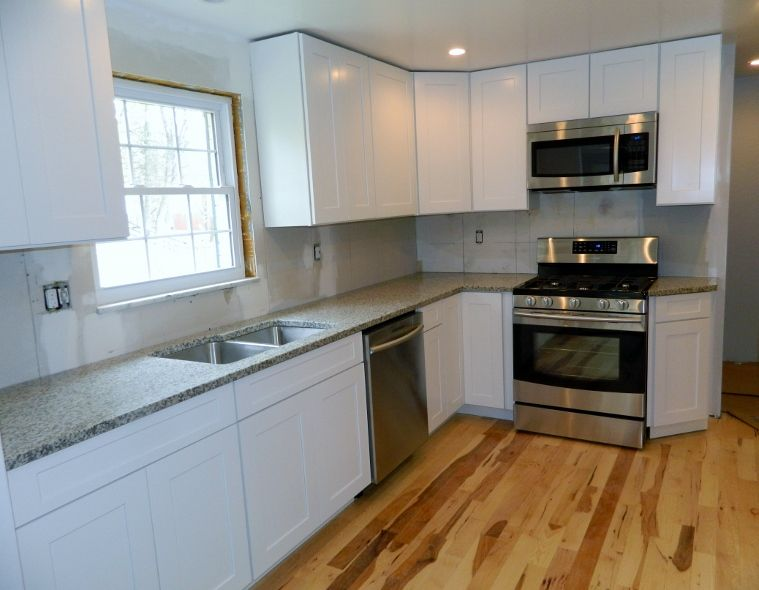 White cabinets with luna pearl granite get installed for Pearl white kitchen cabinets