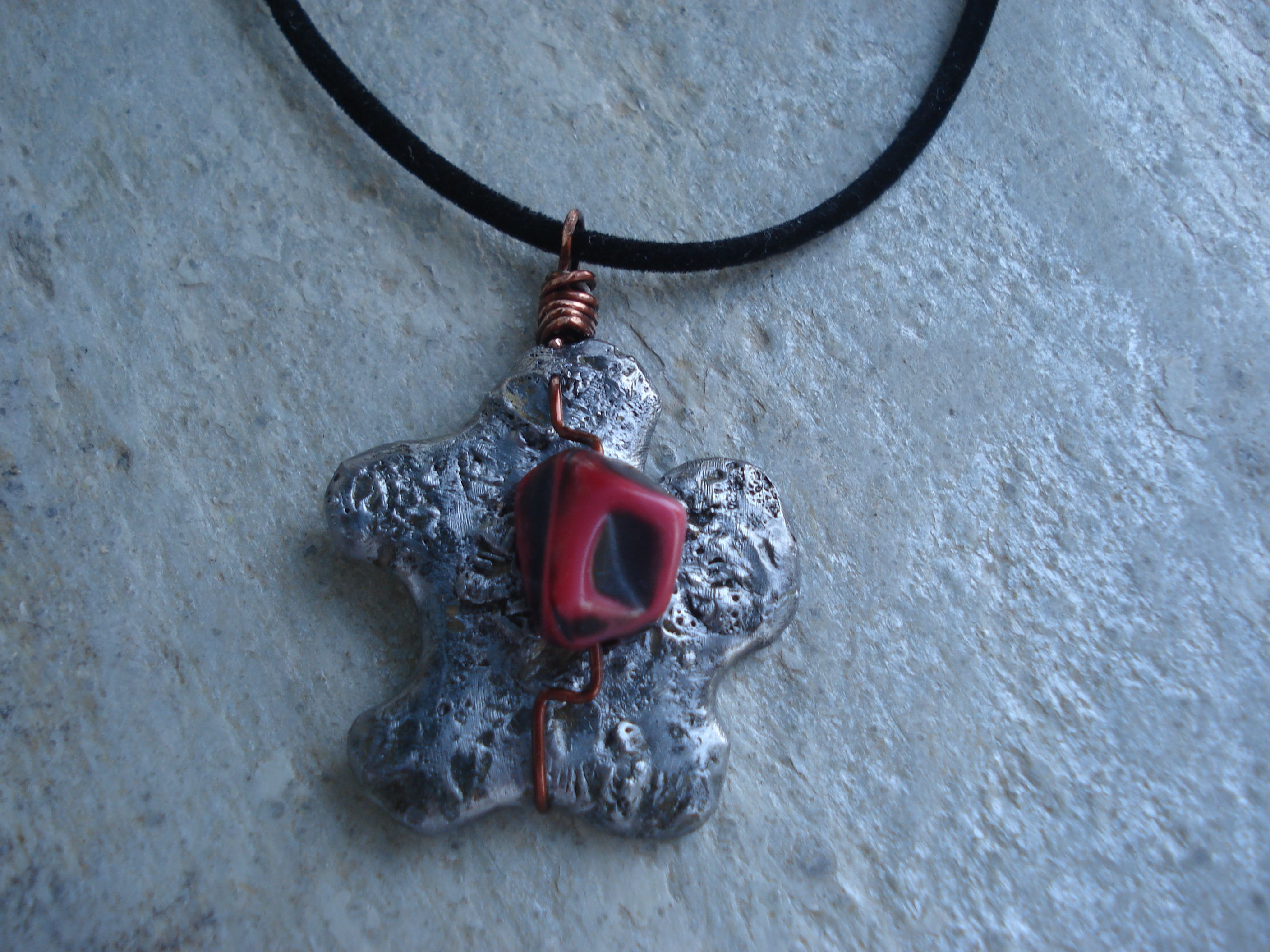 melted lead formed to a flower wire wrapped pendant