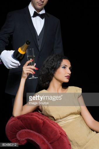 Stock Photo : Woman having champagne served by servant