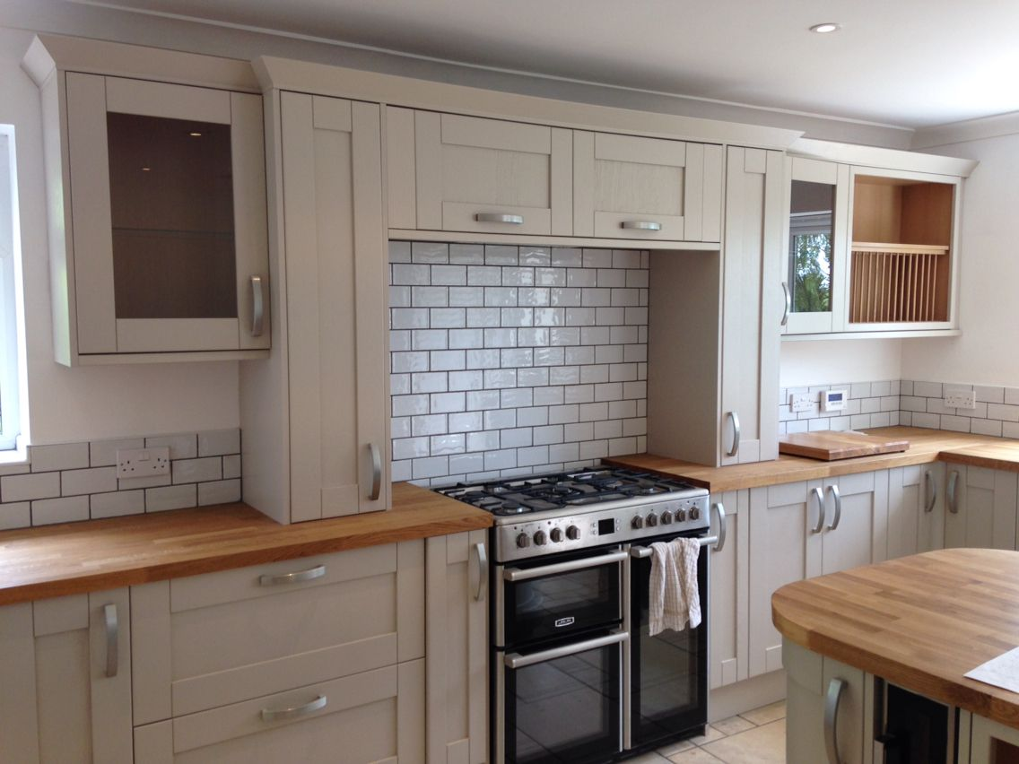 grey coloured kitchen with solid oak worktop and white brick