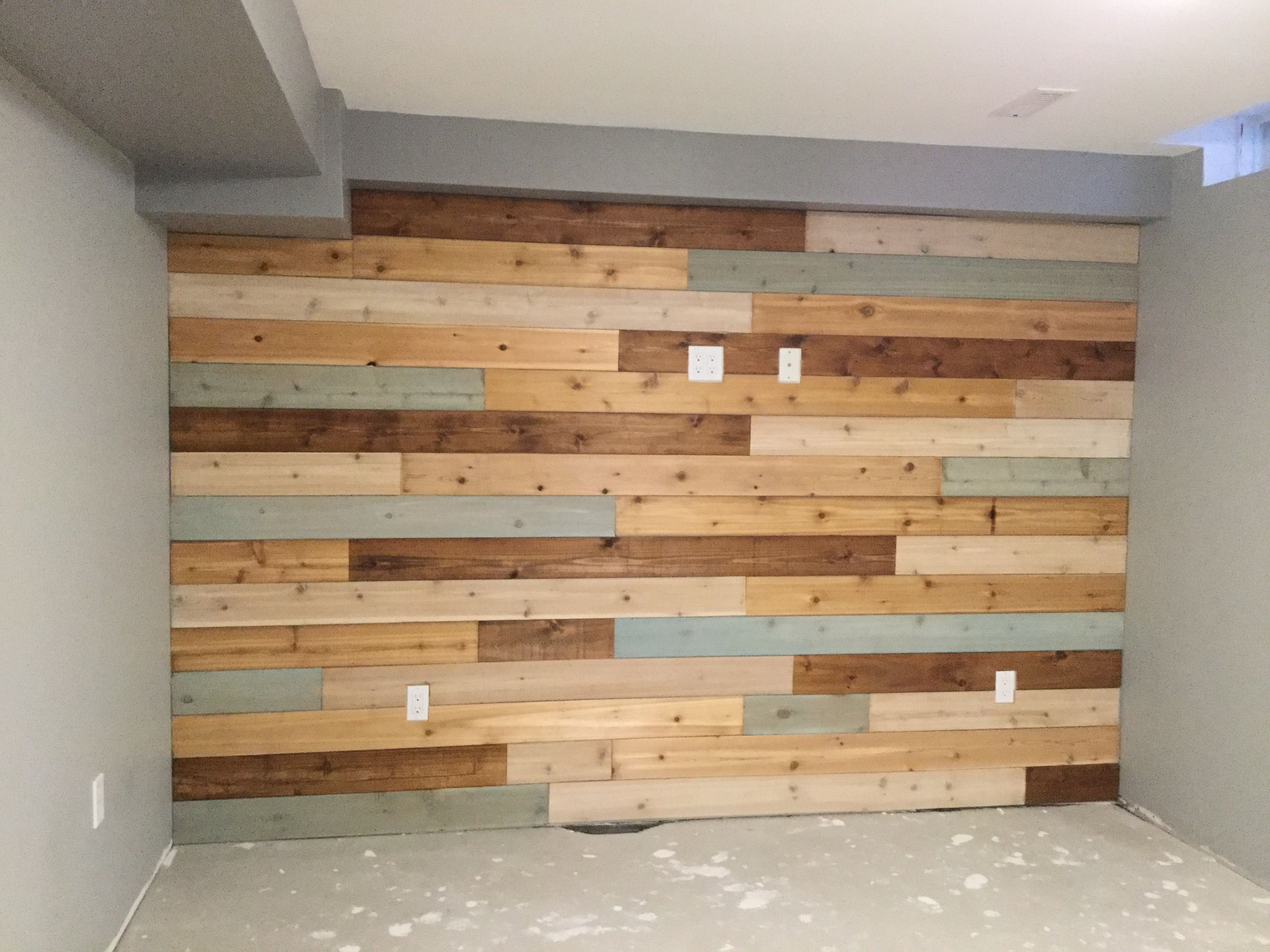Basement wall finished with cedar boards and different finishes
