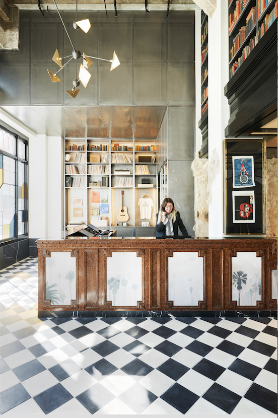 Located in the United Artists building and crafted by design firm Commune, the Ace Downtown LA's lobby features a reclaimed wood desk and black and white checked flooring.  #hospitalitydesignmagazine #hospitalitydesign #hdmag #places #design #designer #hotels #interview #bradwilson #acehotel