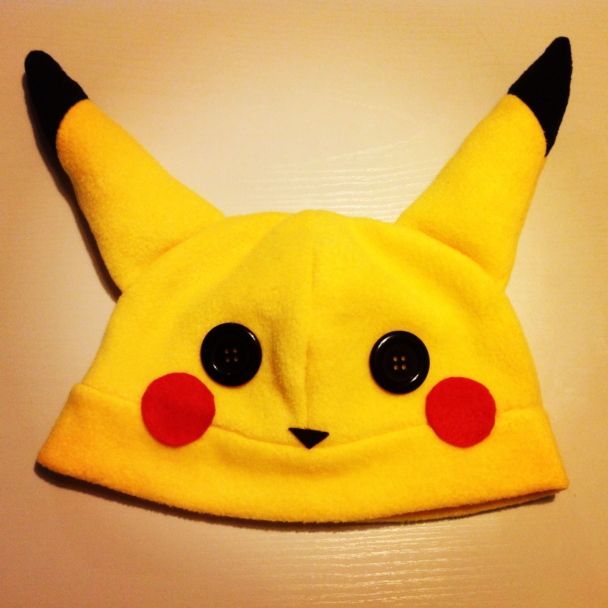 A Pikachu beanie/plushy hat! It's made out of soft, kind of stretchy polar fleece! The blush marks and nose are made out of felt, and is securely hot glued on. The eyes are black buttons, and are also securely affixed with hot glue.    The ears are stuffed with hobby fill, and are soft and squish...