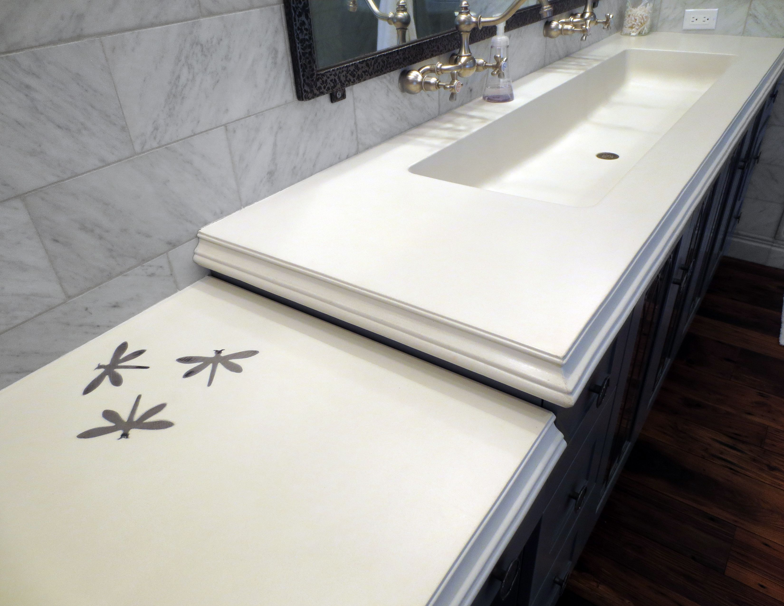 White concrete bathroom sink with steel dragonfly inlays