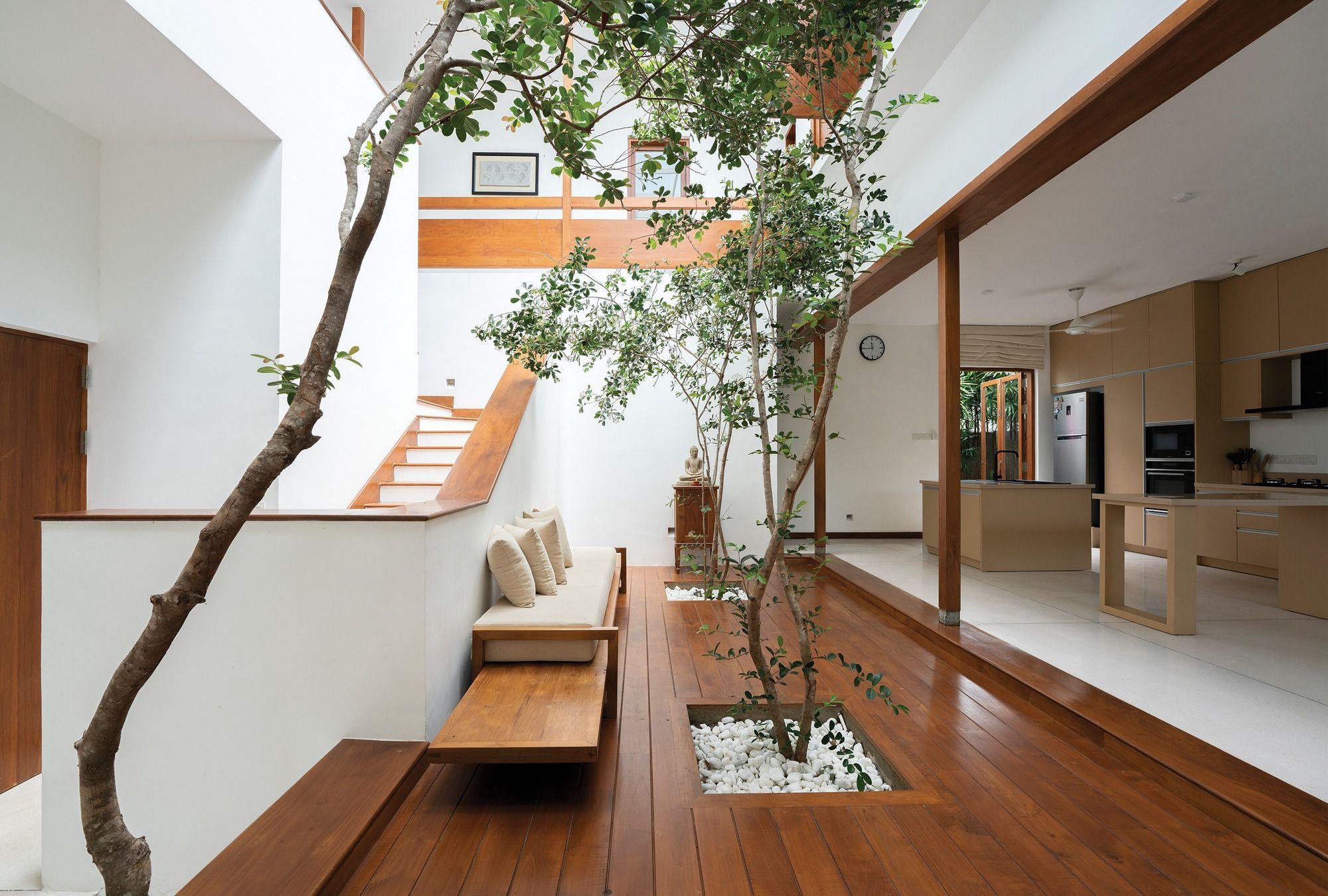 Open plan living spaces centered around a brightly lit indoor courtyard with trees Sri Jayawardenepura Kotte Sri Lanka [2000×1350]