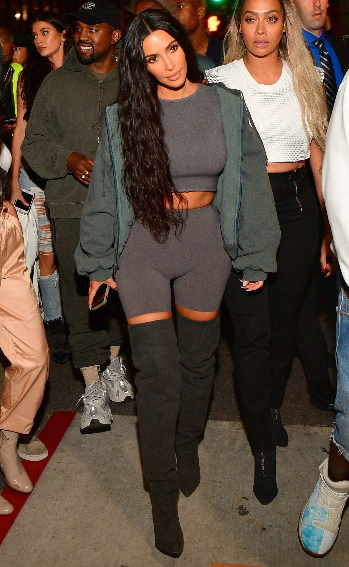 a1d31855115ce Kim Kardashian in a sweatshirt crop top with biker shorts and a green jacket