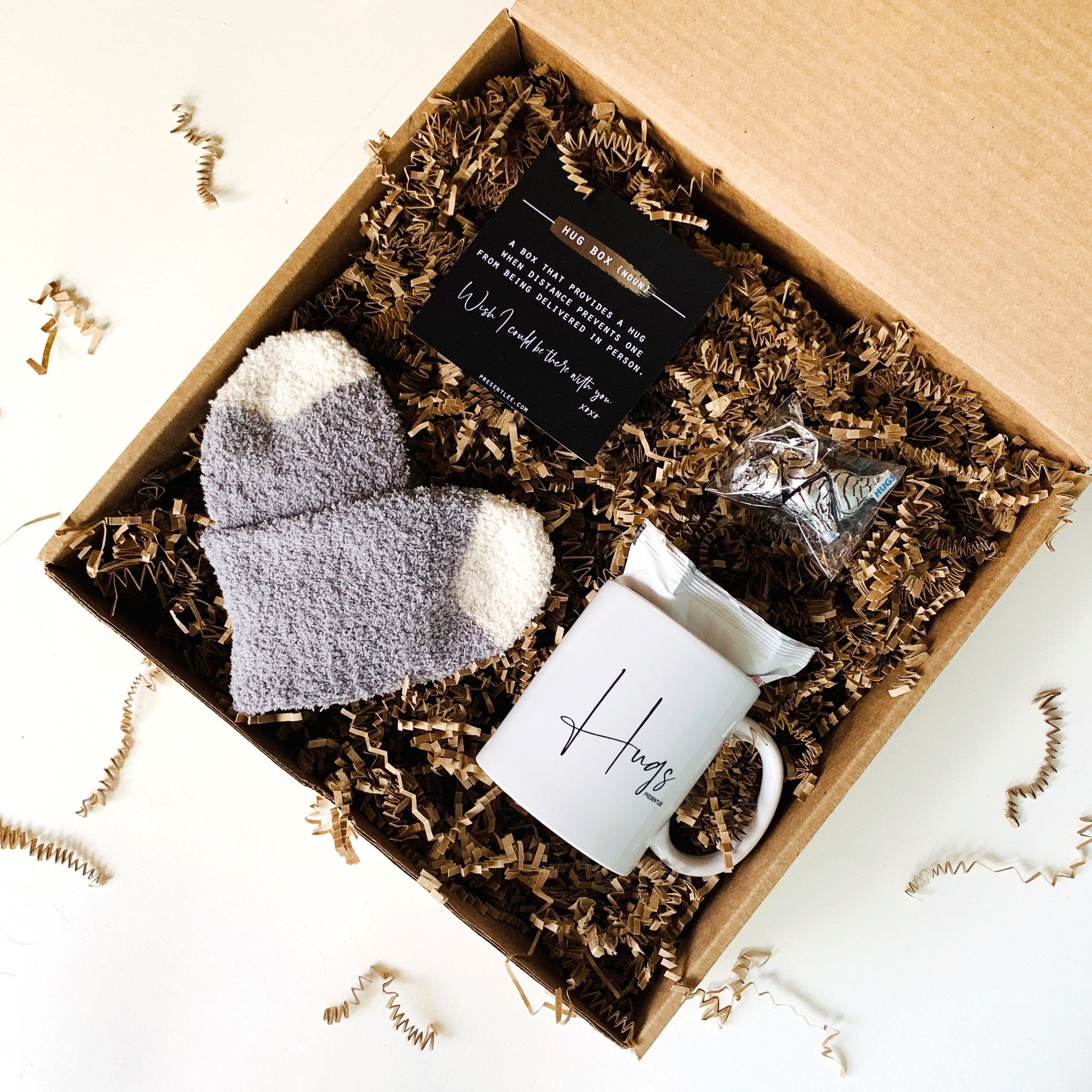 Sometimes a hug is worth more than a thousand words. It helps the other person know beyond a doubt that they matter. This box is the perfect gift for so many different situations. Each box includes: A comfy pair of gray and white fuzzy socks A custom