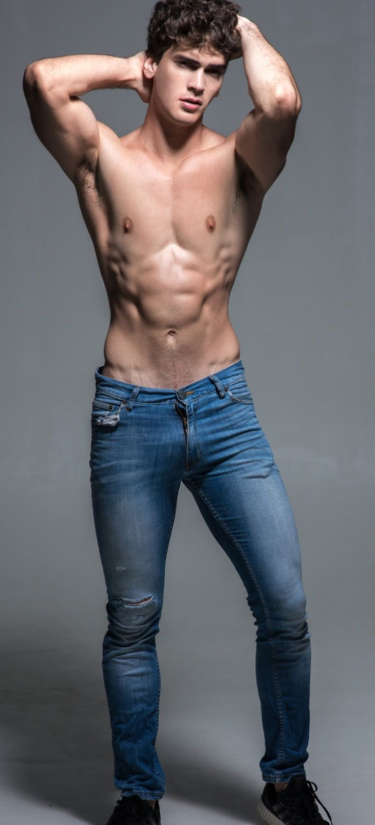 Close Up Of A Fit And Male In Classic Blue Jeans And Black