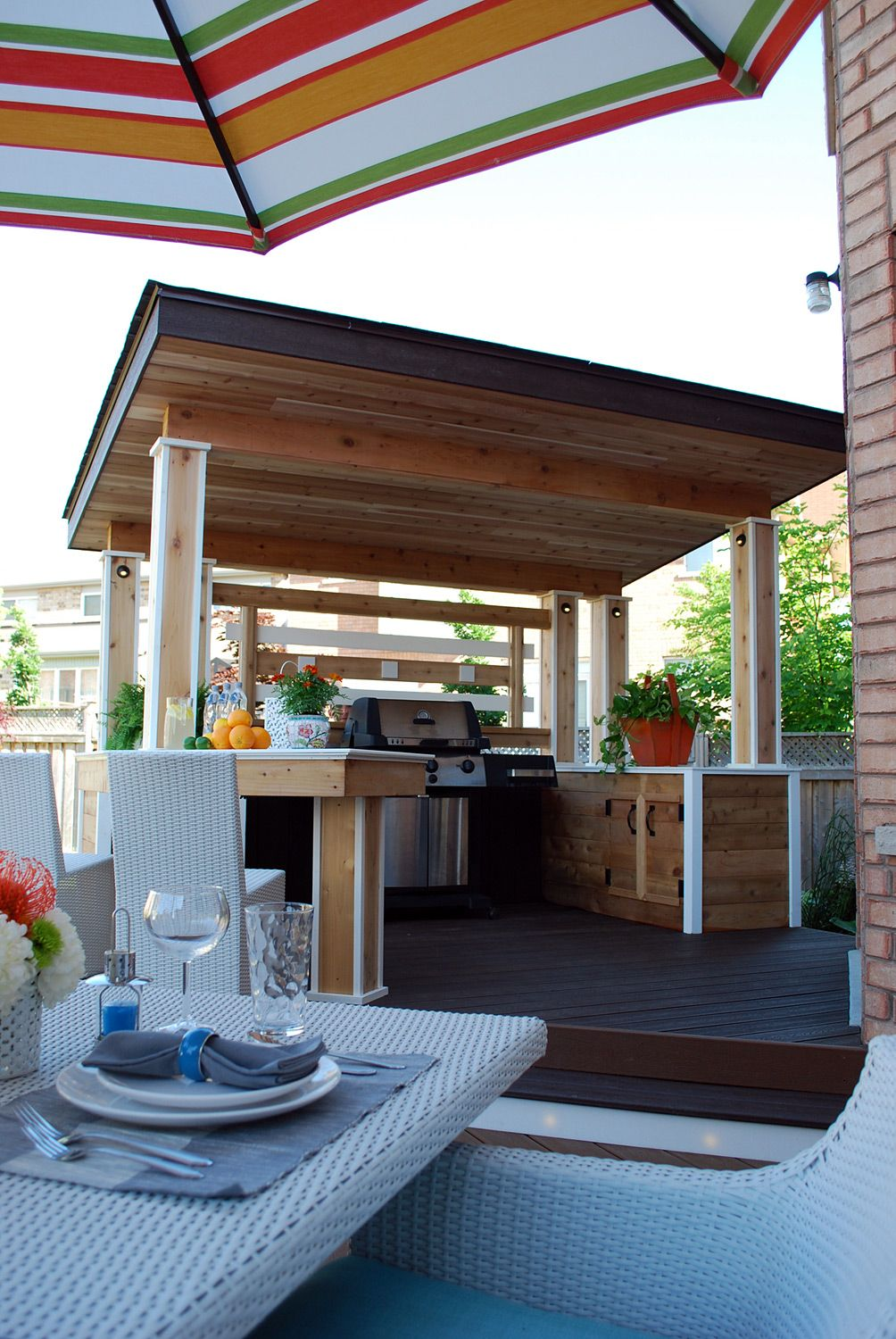 a luxurious outdoor kitchen sheltered by a sloped roof with generous counter space and built. Black Bedroom Furniture Sets. Home Design Ideas