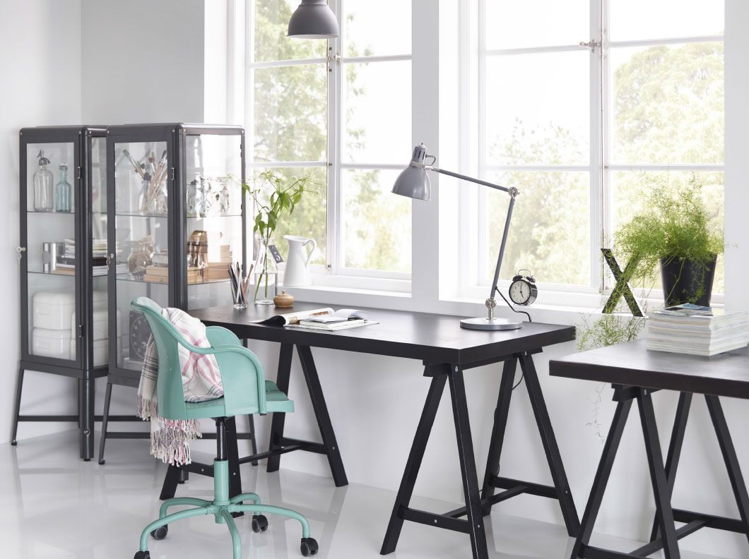 A home office with TORNLIDEN desk in black, black FABRIKÖR glass cabinet and ROBERGET swivel chair in blue