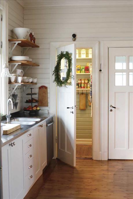 Köket har ett gammaldags skafferi som man kan gå in i och som sväljer allt som man vill förvara svalt. Överst på hyllan närmast fönstret står en keramikskål av Karin Eriksson. Våningsfatet på diskbänken från Cosas. Skärbräda köpt på Sätergläntan i Dalarna.