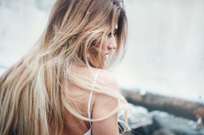 cheveux ombré longs avec racines châtain clair, jeune femme au bord de la mer habillée en robe blanche avec bretelles