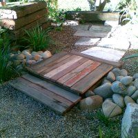 Reclaimed timber bridge crosses a dry stone creek, kids size structures. Edible kids gardens.com.au