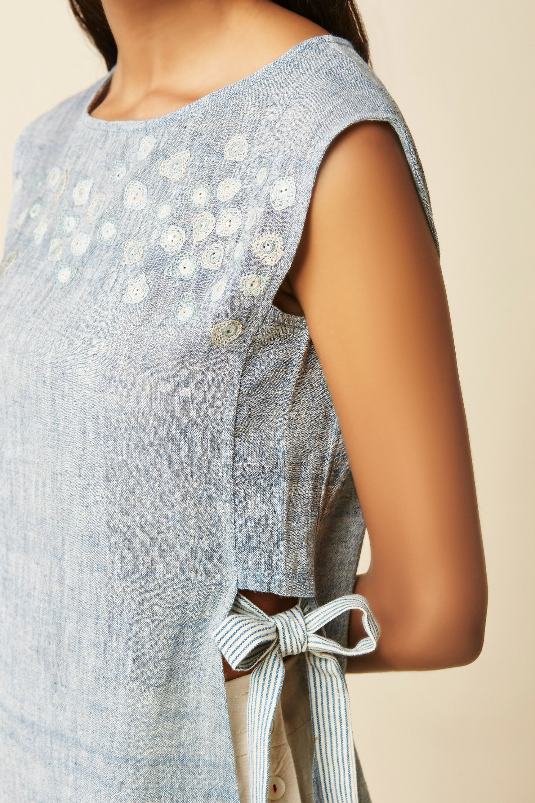 A sleeveless cotton top with slightly extended shoulders intricate