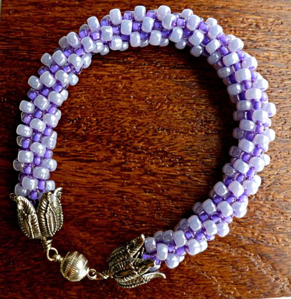 Light purple or lilac colored beaded Kumihimo braided bracelet is just right for spring. The size will fit up to a 6.5 inch wrist with a silverplate magnetic clasp for ease of wear. The seed beads are lightweight and feel cool against the skin. Not shown, a 2 inch safety chain for security in wearing.  Notice the larger light purple beads are mixed in with the smaller darker purple seed beads to create a unique color combination.  Not what you are looking for? See my complete listing of…