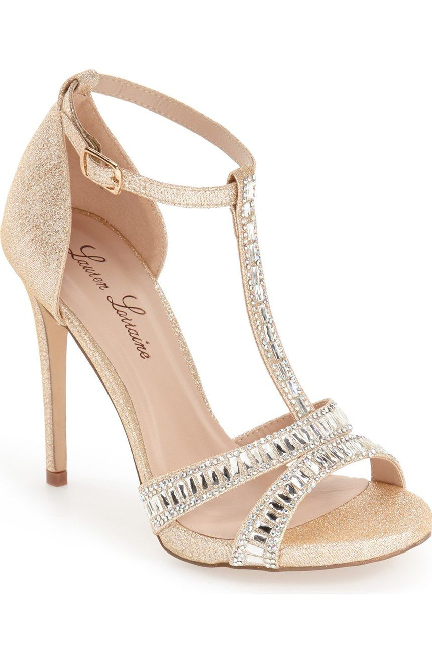 Dazzling crystals highlight this glittery T-strap sandal lifted by a sky-high slender heel and finished with a skinny ankle strap. Lauren Lorraine