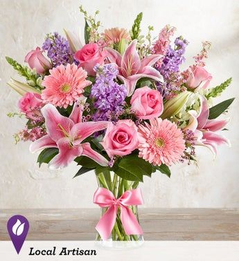 A beautiful bouquet for a worthy cause. In honor of Breast Cancer Awareness month, our florists have arranged a mix of soft pink blooms, with hints of purple and white, inside a glass gathering vase. Finished with a symbolic pink satin ribbon, it's a gift that delivers hope, support, love and comfort to someone you care about. All-around arrangement with pink roses, Oriental lilies, Gerbera daisies and larkspur; white snapdragons; lavender stock; purple waxflower; accented with assorted greenery