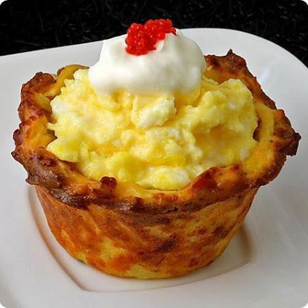 BREAKFAST CUPCAKES 1 20 ounce package pre-shredded hash brown-style potatoes 2 large eggs, lightly beaten 4 tablespoons flour 1 small sweet onion, coarsely grated 2 thick slices deli ham, chopped into small bits (about 1 cup) 1 cup shredded mozzarella cheese ½ cup grated Parmesan cheese Salt and freshly ground black pepper to taste 1 dozen eggs, scrambled* chives for garnish