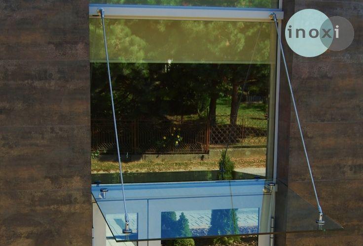 Daszek szklany podwieszany na cięgnach firmy INOXI - mocowany do stolarki aluminiowej.
